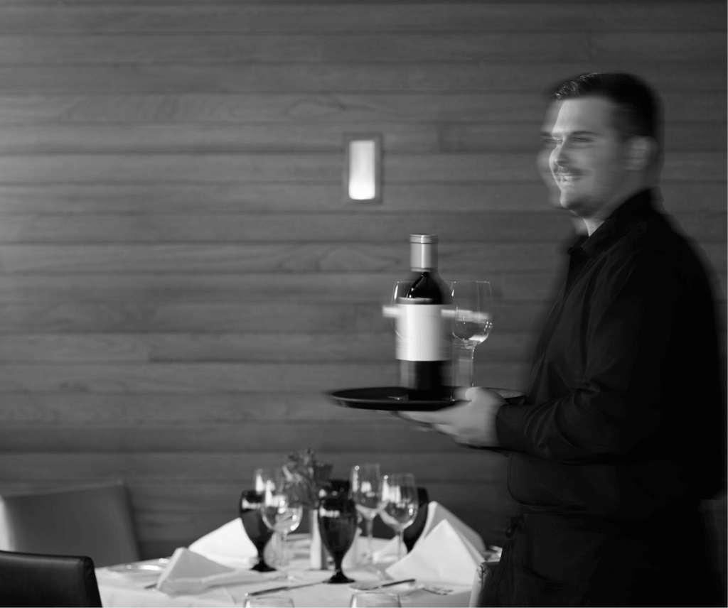 A server carries wine though the dining room at Pier W Restaurant and Lounge