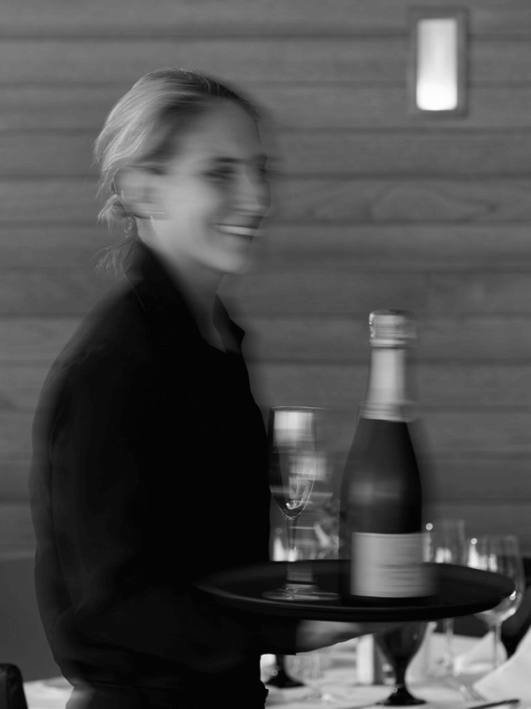 A server carries champagne through the dining room of Pier W.