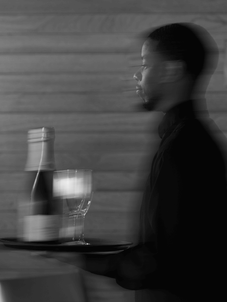 A server carrying champagne through the dining room at Pier W